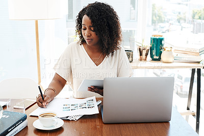 Buy stock photo Shot of a young businesswoman writing notes while working on a digital tablet in an office