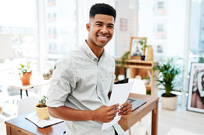 Buy stock photo Portrait of a confident young businessman going over paperwork in a modern office