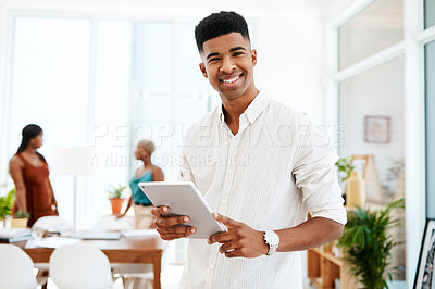 Buy stock photo Portrait of a young businessman using a digital tablet in a modern office