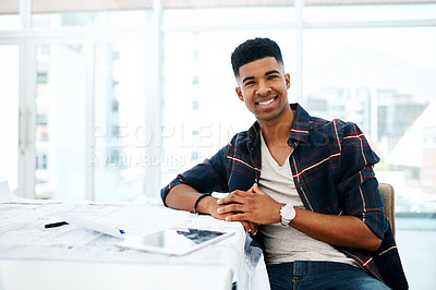 Buy stock photo Portrait of a young man going over blueprints in a modern office
