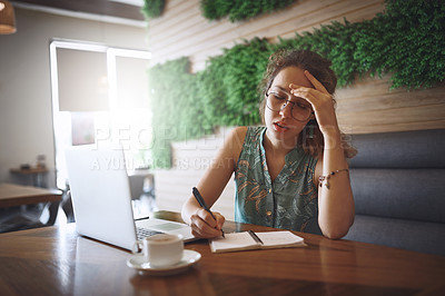 Buy stock photo Shot of a young woman looking stressed while working at a cafe