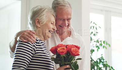 Buy stock photo Cropped shot of a senior man spoiling his wife with roses at home
