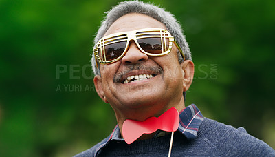 Buy stock photo Portrait of a senior man wearing fun glasses at the park