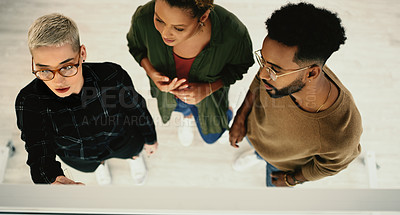 Buy stock photo High angle shot of a group of businesspeople brainstorming with notes on a glass wall in an office