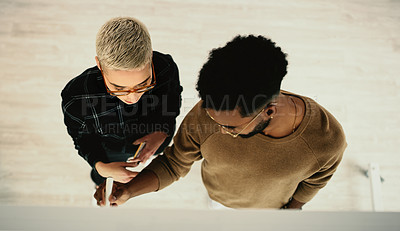 Buy stock photo High angle shot of two businesspeople brainstorming with notes on a glass wall in an office