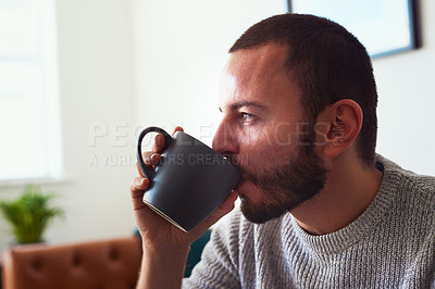 Buy stock photo Shot of a young man drinking coffee while relaxing at home