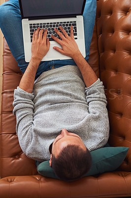 Buy stock photo High angle shot of a young man using a laptop while relaxing on a sofa at home