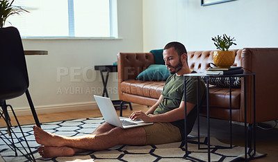 Buy stock photo Shot of a young man using a laptop while sitting on the floor at home