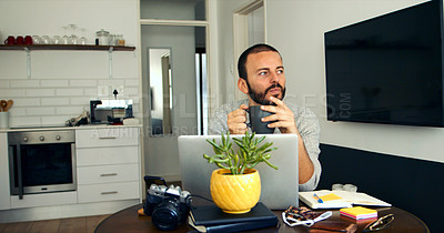 Buy stock photo Shot of a young man drinking coffee while working on a laptop at home