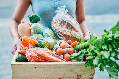 Buy stock photo Cropped shot of a woman delivering a crate full of groceries