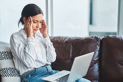 Buy stock photo Shot of a young woman using a laptop on the sofa and looking stressed while working from home