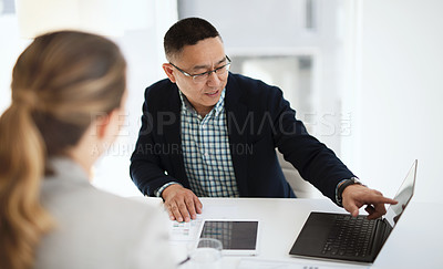 Buy stock photo Shot of a businesswoman and businessman using a laptop in a modern office