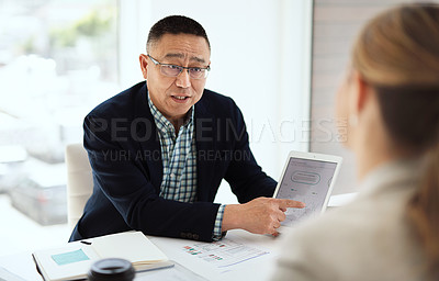 Buy stock photo Shot of a businesswoman and businessman using a digital tablet in a modern office