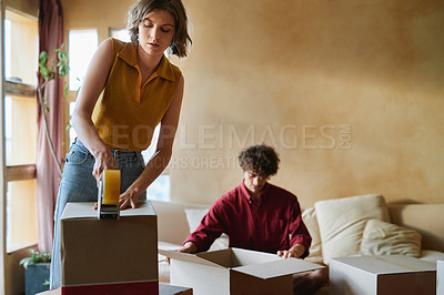 Buy stock photo Shot of a young couple packing boxes in their home