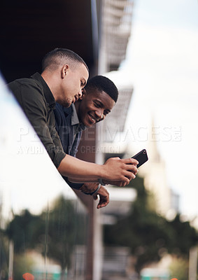 Buy stock photo Shot of two businessman looking at something on a cellphone while standing on the balcony of an office