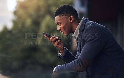 Buy stock photo Shot of a young businessman using a cellphone while standing on the balcony of an office