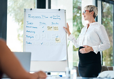 Buy stock photo Shot of a pregnant businesswoman using a whiteboard while giving a presentation in an office