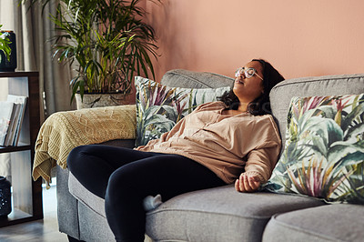 Buy stock photo Shot of a young woman resting on the sofa at home