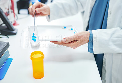 Buy stock photo Cropped shot of a pharmacist filling a prescription of capsules in a chemist