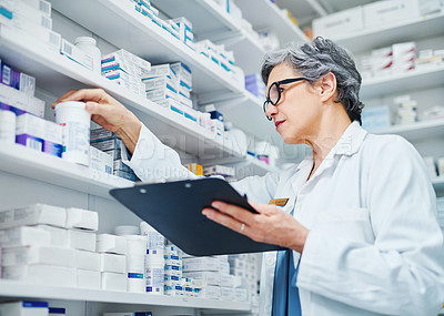Buy stock photo Shot of a mature woman filling a prescription while working in a chemist
