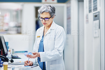 Buy stock photo Shot of a mature woman filling out a prescription in a pharmacy