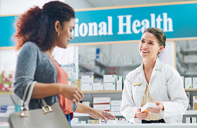 Buy stock photo Shot of a young pharmacist assisting a customer in a chemist