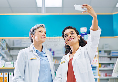 Buy stock photo Shot of two pharmacists taking selfies in a chemist