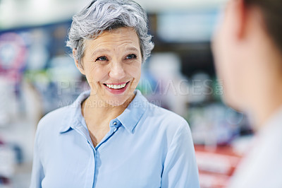 Buy stock photo Shot of a pharmacist assisting a mature woman in a chemist