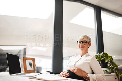 Buy stock photo Portrait of a pregnant businesswoman sitting at a desk in an office
