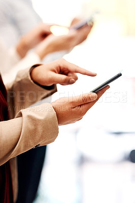 Buy stock photo Closeup shot of an unrecognisable businesswoman using a cellphone with her colleague in the background