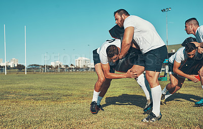 Buy stock photo Shot of rugby players training with tackle bags on the field