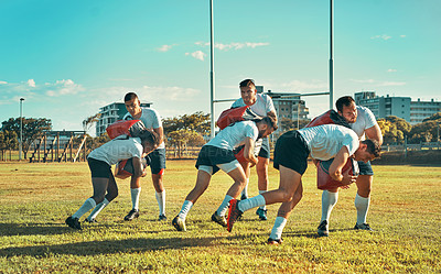 Buy stock photo Shot of a group of rugby players training with tackle bags on the field
