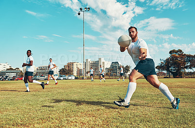 Buy stock photo Shot of young men playing a game of rugby on a field