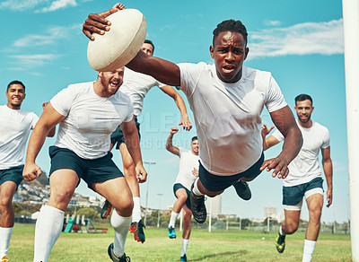 Buy stock photo Shot of a rugby player scoring a try while playing on a field