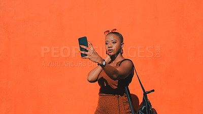 Buy stock photo Shot of an attractive young woman taking selfies against an orange wall in the city