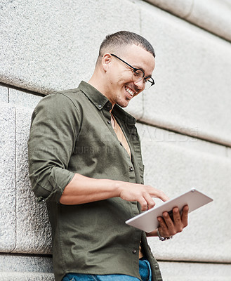 Buy stock photo Shot of a young businessman using a digital tablet against an urban background