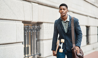 Buy stock photo Shot of a young businessman holding a skateboard while walking through the city