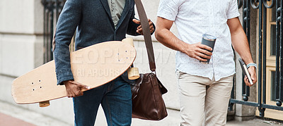 Buy stock photo Cropped shot of two young businessmen walking through the city together