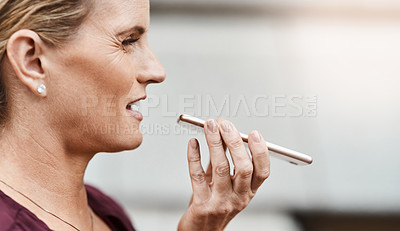 Buy stock photo Shot of a mature businesswoman using a smartphone against an urban background