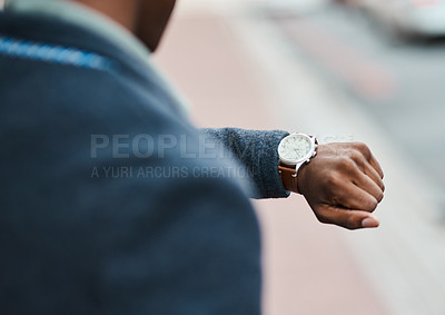 Buy stock photo Cropped shot of a businessman checking the time against an urban background