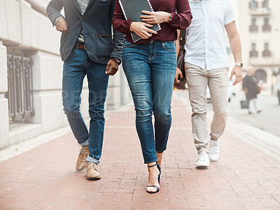 Buy stock photo Shot of a group of unrecognisable businesspeople walking through the city