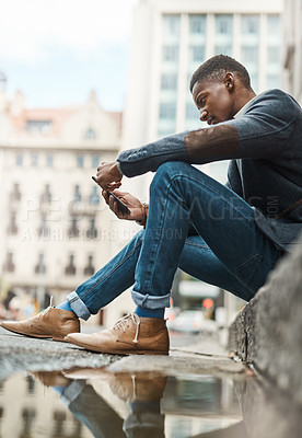 Buy stock photo Shot of a young businessman sitting on the curb and using a smartphone against an urban background