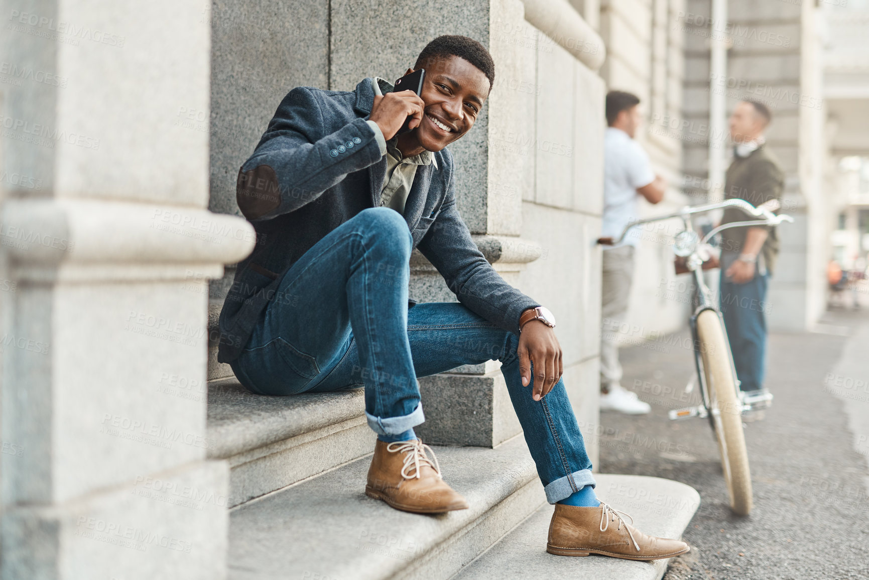 Buy stock photo Shot of a young businessman using a smartphone against an urban background