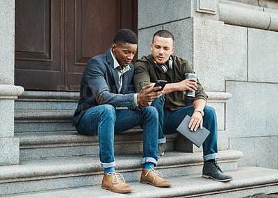 Buy stock photo Shot of two young businessmen using a smartphone together against an urban background