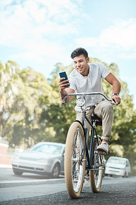 Buy stock photo Shot of a young businessman using a smartphone while riding his bicycle in the city