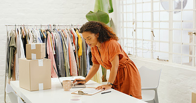 Buy stock photo Shot of a young woman organising deliveries in a design studio