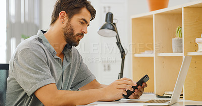 Buy stock photo Shot of a young businessman using a smartphone and laptop at his desk in a modern office