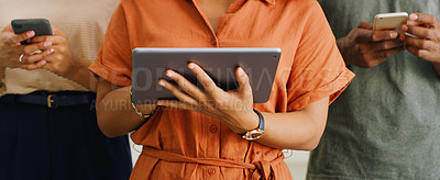 Buy stock photo Cropped shot of a group of businesspeople using their smart devices in a modern office