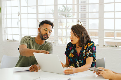 Buy stock photo Shot of a young businessman and businesswoman using a laptop during a meeting in a modern office