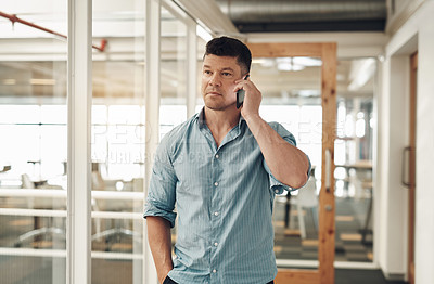 Buy stock photo Cropped shot of a handsome young businessman using his cellphone while standing in the office